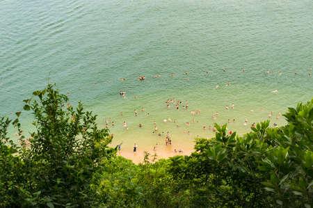 해변에서 수영하는 정체 불명 한 사람들의 공중보기. 여름 휴가 배경 스톡 콘텐츠