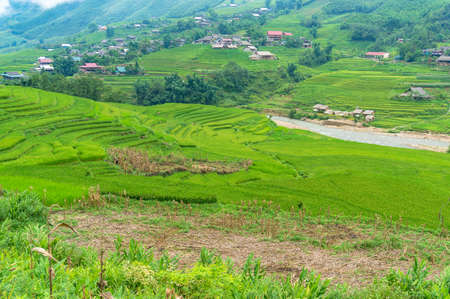 Rice terraces and fields with village in the distance. Countryside landscape Stock Photo