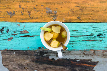 Cup of tea with ginger pieces and lemongrass stalk on old painted table. Shabby background