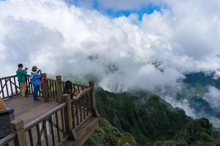 SaPa, Vietnam - August 20, 2017: Tourists enjoying the view from observation deck on Fansipan mountain summit in Vietnam