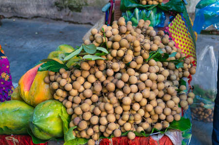 Pile of langsat fruits on street market. Exotic tropical fruits background