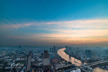 Aerial view of Bangkok cityscape with Chao Phraya river at sunset. Urban sprawl background