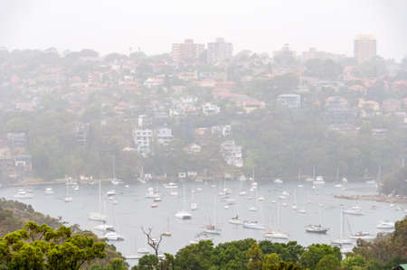 Sydney suburb with picturesque bay with yachts in the rain