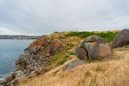 Coastline with high cliff covered with rocks and colorful lichen nature background. Granite island