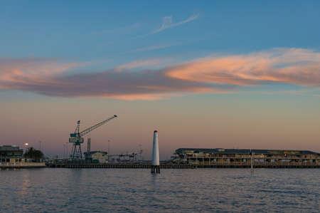 Wharf with hoisting crane and lighthouse at dusk. Nautical, sea port landscape background