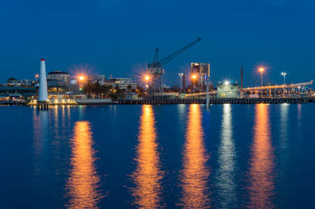 Wharf with crane, machinery and lighthouse at night. Nautical, sea port landscape background. Port Melbourne, Australia