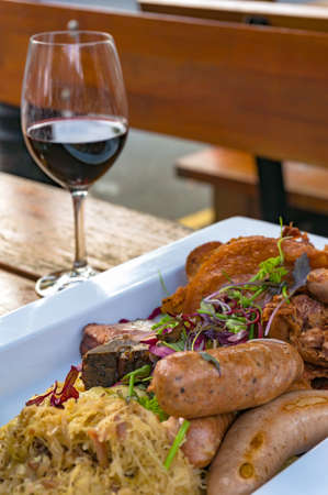 German sausages with meat, vegetables and sauerkraut, cabbage with glass of red wine on the background. Al fresco restaurant dinning food background Stock Photo