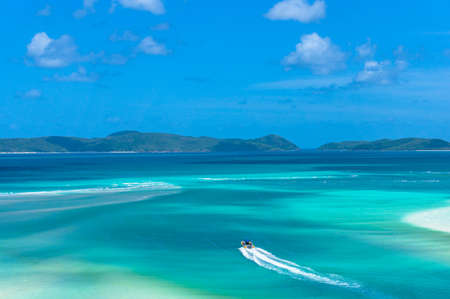 Aerial view of rafting boat on turquoise blue water of tropical coral reef sea on low tide