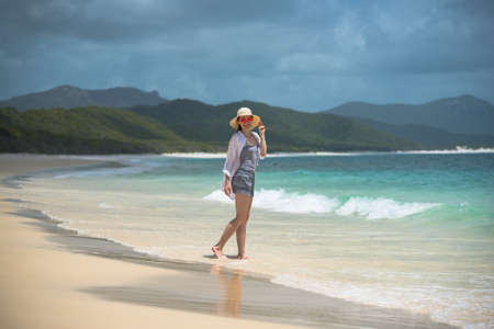 Beautiful woman posing and smiling on a tropical beach. Queensland, Australia Stock Photo