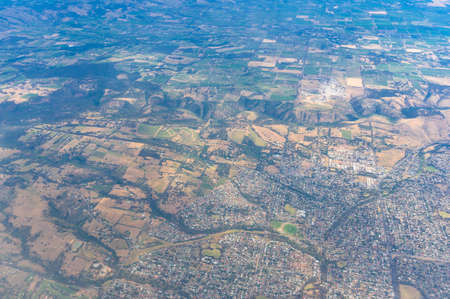Aerial view on rural farmland with fields, pastures and urban sprawl. South Australia