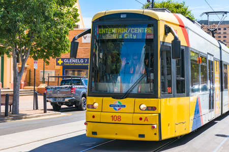 Glenelg, Australia - November 13, 2017: Bright yellow tramway with friendly driver waving his hand. Public transport of South Australia. Glenelg, Australia