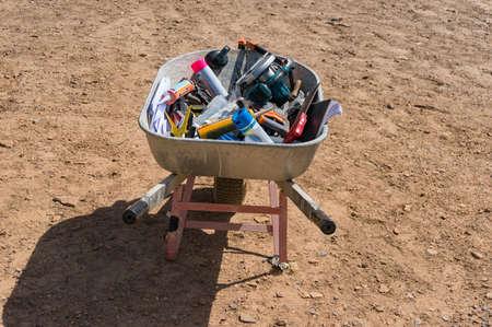 Wheelbarrow with construction, building tools on dirt ground