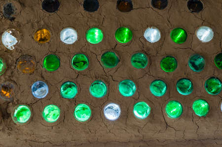 Colorful sunlit bottles in a clay cob wall, bottle wall mosaic. Ecological building from natural and recycle materials