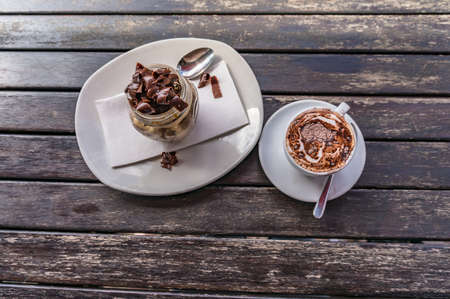 Appetizing chocolate dessert and cup of coffee on wooden table in outdoor cafe
