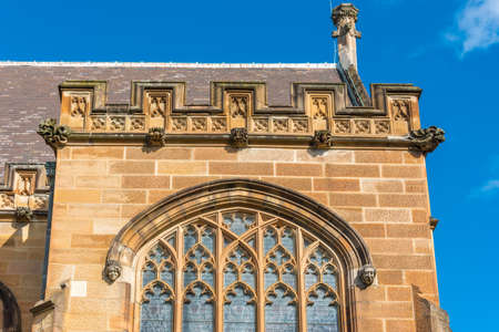 Sandstone gothic building with arch windows and gothic decorations
