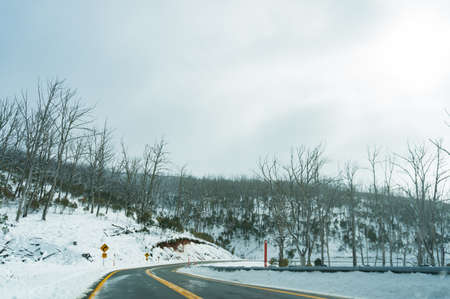 Winter landscape with winding road covered with snow. Transportation in winter landscape