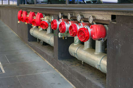 Bright hydrant boosters in a row with metal pipes and red caps. Industrial urban infrastructure Stock Photo