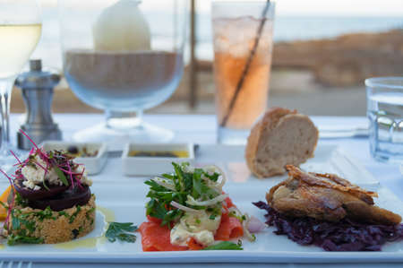 Restaurant table with served entree plate with small snacks. Al fresco fine dining settings with water view