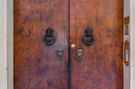Old wooden door with intricate door handles and door knockers. Historic architectural details