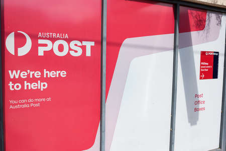 Sydney, Australia - April 14, 2019: Australia Post post office boxes and shop advertisement sign in Miranda suburb of Sydney 報道画像