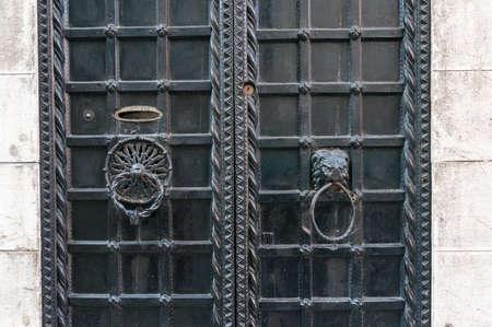 Closed old metal door with cast iron lattice and metal door handles, knockers
