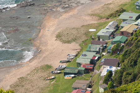 Aerial view of fishing houses with solar panels and junk boats at a beach on a shore. Otford, Australia