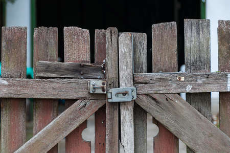Close up of old farm gate with the metal door latch. Closed weathered plank paddock door Stock Photo