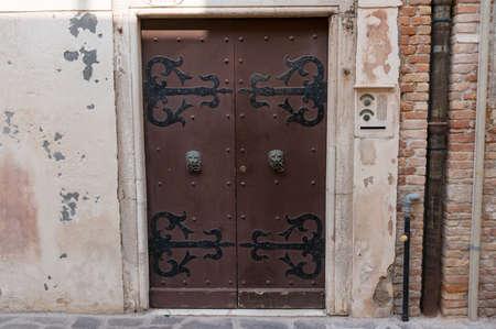 Old vintage door with metal hinges and door handles. Historic architectural detail background