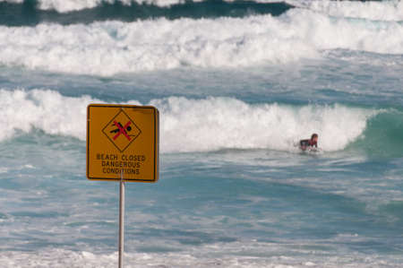 A warning sign of closed beach with person surfing rough waves on the background. Rebellion, disobedience concept