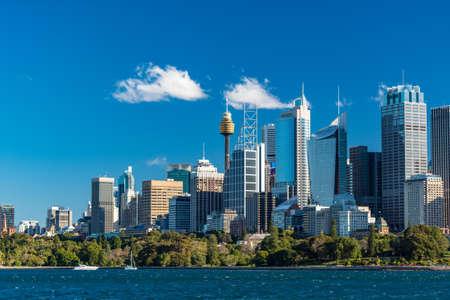 Sydney Harbour und weiße Yachten mit Sydney Skyline im Hintergrund. Sydney Tower und Sydney Business District Wolkenkratzer an einem sonnigen Tag. Modernes Stadtbild