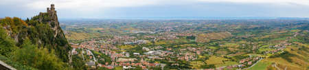 Aerial panorama of First tower of San Marino, Guaita castle on the cliff edge of Monte Titano with vast rural landscape view. San Marino