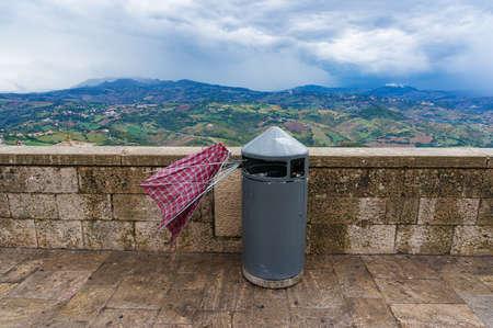 Broken umbrella in rubbish bin. Rainy weather, misfortune concept, metaphor