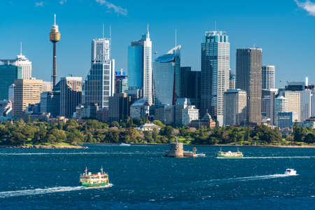 Sydney cityscape view with yachts and ferries over Sydney Harbour on sunny day Stok Fotoğraf