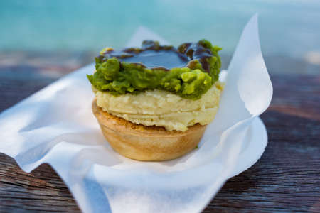 Australian traditional meat pie with mashed potatoes, green peas and gravy in pastry case with Fingers Wharf on the background. Woolloomooloo, Sydney, Australia