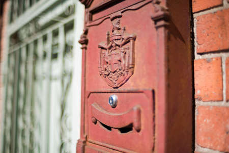 Red post box, letterbox with Swiss heraldic coat of arms