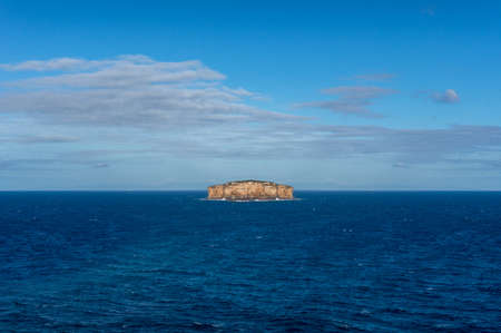 Isolated lonely island surrounded with deep blue ocean waters. NAture background