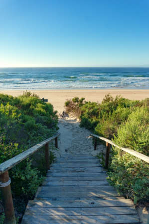Ocean view beach background with wooden path covered in sand. Summer tropical beach vacation scene