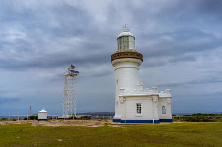 White lighthouse building architecture with overcast sky on the background. Point Perpendicular lighthouse in Beecroft Peninsula in Australia Imagens
