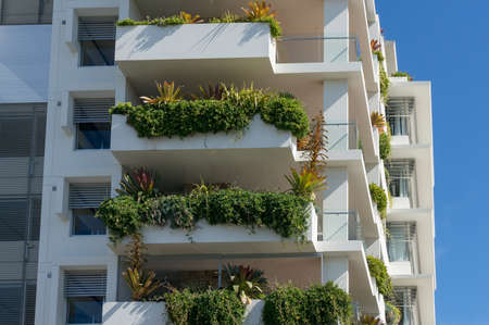 Green plants growing on the balconies of white building. Architecture ecology design in urban places
