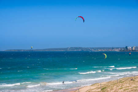 Vast ocean landscape with people kitesurfing on waves. Summer water sport activities Standard-Bild