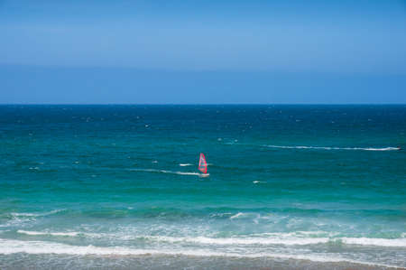 Ocean landscape with bright wind surfing sail. Summer water sports