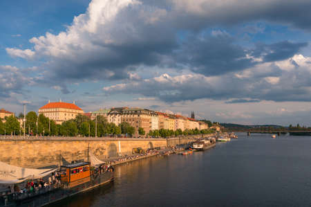 Prague, Czech Republic - May 22, 2018: Prague waterfront with restaurants and tourists and waterview buildings