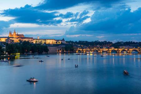 Vltava river with boats, Charles bridge and illuminated Prague castle at blue hour Фото со стока