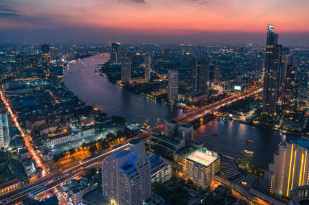 Aerial view of epic sunset sky above Bangkok cityscape and Chao Phraya river. Birds eye view of night Asian city with busy traffic