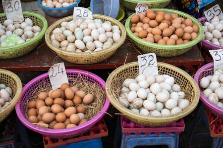 Variety of chicken eggs in a baskets with straw for sale on street market in Vietnam, Asia Stock Photo
