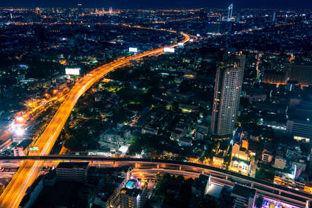 Aerial view of night modern city with light trails on the highway from the traffic. Bangkok, Thailand Stock Photo
