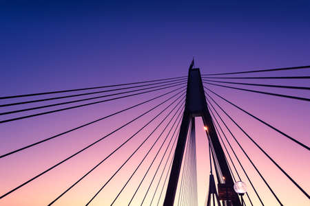 Abstract architecture background of bridge ropes, rods silhouettes against violet and blue sunset sky Stock Photo