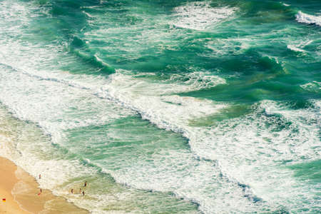 Aerial view of massive ocean waves and people on the beach. Tropical summer beach holiday background Stock Photo
