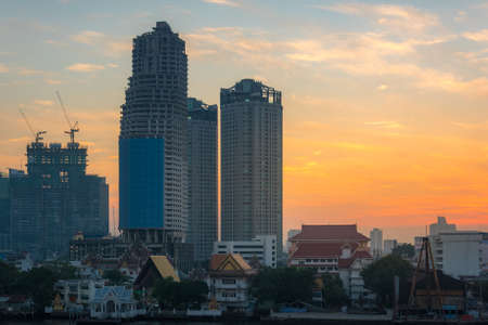 Bangkok cityscape with waterfront property and unfinished skyscrapers construction. Property crysis in capital cities Stock Photo