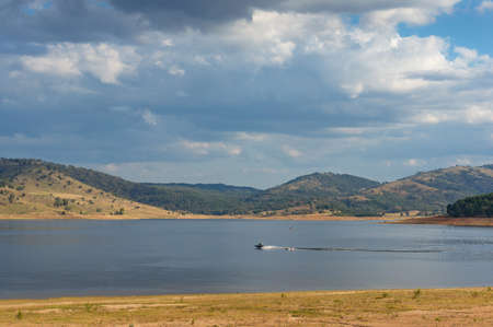 Nature landscape with lake and fishing motor boat against picturesque hills on the background. Wyangala nature park, Australia